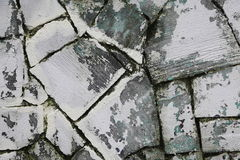 A fragment of the old wall of sawn natural stone grey Sandstone with traces of whitewash peeling lime white. Stock Image