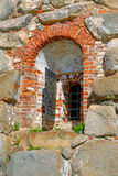 A fragment of the old wall with window and bars Stock Image