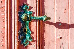 old weather-beaten red door with old vintage door knob, surface with chapped textured paint Stock Photography