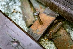 Fragment of old wooden brown broken bench with spike in it. Old rusted wooden bench with spike royalty free stock photos