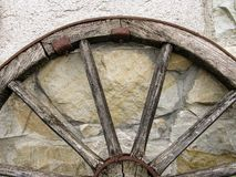 Fragment of an old wooden cartwheel against a wall of natural stone. royalty free stock images