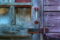 A fragment of an old wooden door. With a handle on the locked padlock Royalty Free Stock Photography