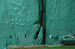 Fragment of an old wooden door with a nail. Fragment of an old wooden door painted green paint Stock Photo