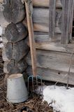 Fragment of an old wooden house. Bucketful and forks are near your old home Stock Photos