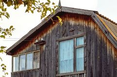 Fragment of an old wooden house. Roof window and roof stock photo