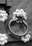 Fragment of an old forged door, door handle. A fragment of an old wrought iron door with a lock and ornaments in the form of sockets Stock Image