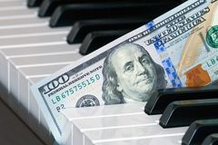 Fragment of one hundred dollar bill into the piano keys. View of a fragment of one hundred dollar bill, a new sample, inserted into the piano keys concept Royalty Free Stock Photography