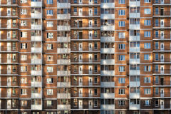 Fragment of one of the serial high-rise apartment buildings in Moscow suburbs with the sunset glare on the wall and Stock Photos