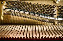Fragment of open upright piano mechanism with strings and hammers royalty free stock photo