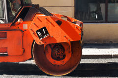 Fragment of orange roller, urban road is under construction Stock Photos