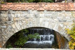 Fragment of the outer wall with a small waterfall located near  Pelesh castle in Sinaia, in Romania Stock Images
