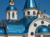 The beautiful building of the white church of the Orthodox faith shines in the sun. The fragment, part of the Orthodox church, shimmers with its blue roof stock photo