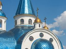 The beautiful building of the white church of the Orthodox faith shines in the sun. The fragment, part of the Orthodox church, shimmers with its blue roof royalty free stock image