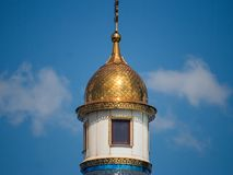 The beautiful building of the white church of the Orthodox faith shines in the sun. The fragment, part of the Orthodox church, shimmers with its blue roof stock image
