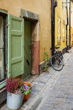 Fragment of paved Swedish streets with flowers by the window, door and the cycle Royalty Free Stock Photos
