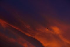 Fragment photo of one airplane going up in dramatic colourful sky background . Airplane in the sky on sunset Royalty Free Stock Image