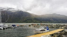 Fragment of the pier in Surfjorden near the city of Odda, Norway. View of the large mountain plateau with its massive glaciers. royalty free stock image