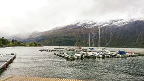 Fragment of the pier in Surfjorden near the city of Odda, Norway. View of the large mountain plateau with its massive glaciers. royalty free stock photos