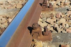 Fragment of a railway bed. Fastening of rails to sleepers with the help of a bolt. Gravel for trains. Technology of transport comm royalty free stock images