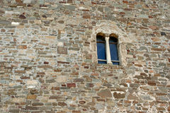 The fragment of the reconstructed stony wall with the small gothic window in the medieval Genoese fortress. Royalty Free Stock Photo