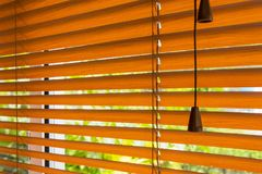Fragment of the red brown Venetian blinds on a window and blurre Stock Photos