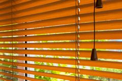 Fragment of the red brown Venetian blinds on a window and blurre Royalty Free Stock Photography