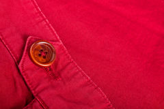 Fragment of red button on cotton twill material. Close up. Copy space. Royalty Free Stock Photo