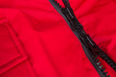 Fragment of red jacket with black zipper. ziplock background. Close up. Royalty Free Stock Photos
