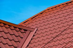 Fragment of red metal tile roof. Fragment of red a metal tile roof surface a background of bright blue sky stock photography