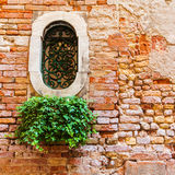 Fragment of red vintage old brick wall with round window. Stock Photos