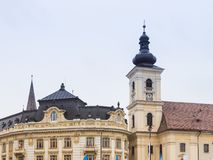 Fragment of the Roman Catholic Church of the Holy Trinity and Sibiu City Hall on the Large Square in Sibiu city in Romania Royalty Free Stock Photos