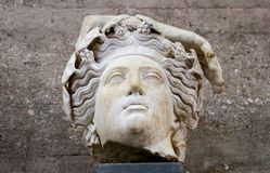 Fragment of roman statue - god from ancient Corinth Greece with flowers or grapes in wavy hair and part of a hand stock image