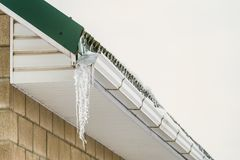 Fragment of roof cornice with overhang icy icicle gutter after thaw. Defective drain stock photo