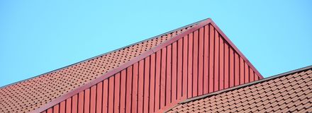 A fragment of a roof from a metal tile of dark red color. Qualit Royalty Free Stock Photos