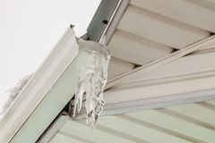 Fragment of roof overhang with icy icicle gutter Stock Photography