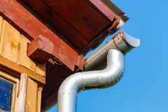 Fragment of the roof of a village house with drainpipe closeup against blue sky royalty free stock photography