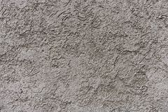 Fragment of a roughly plastered exterior gray wall stock image
