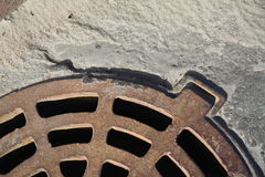 A fragment of rusty cast iron manhole to drain rainwater, concrete. Grey river sand and dust. Stock Photos