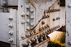 Fragment of rusty metal structures of the old railway bridge. Corrosion and old paint bolts and bridge nuts stock photos