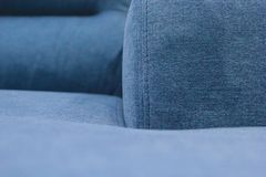 Fragment of the seat, back and armrest of the blue sofa. stock images