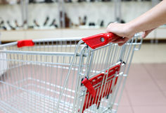 Fragment of shopping cart in shoe store Stock Photos