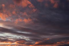 A fragment of the sky in gold and purple tones with clouds at sunset. Beautifu bright fragment of the sky in gold and purple tones with clouds at sunset Stock Photos