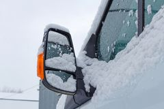 Fragment of snow covered cab of the truck on a winter cloudy sky background Royalty Free Stock Photo