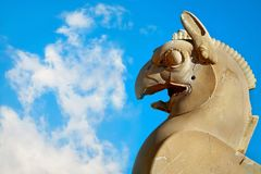 Fragment of stone column sculpture of a Griffin in Persepolis against a blue sky with clouds. Ancient Achaemenid Kingdom. Iran. Persia Stock Photos
