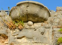 Fragment of stone wall of ruins of fortress of St. John with image of lion, Kotor, Montenegro Stock Image