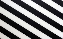 Fragment of a striped black and white piece of a plastic as a background texture stock image