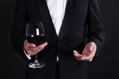 Fragment of stylish man in elegant black tuxedo with glass red w Royalty Free Stock Photo