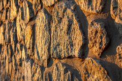 Fragment of sunlit stone wall. Side view. Fragment of sunlit stone wall at sunset. Side view with shallow depth of field Stock Image
