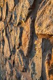 Fragment of sunlit stone wall. Side view. Fragment of sunlit stone wall at sunset. Side view with shallow depth of field Stock Photo
