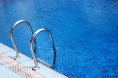 Fragment of swimming pool with ladder Royalty Free Stock Photos